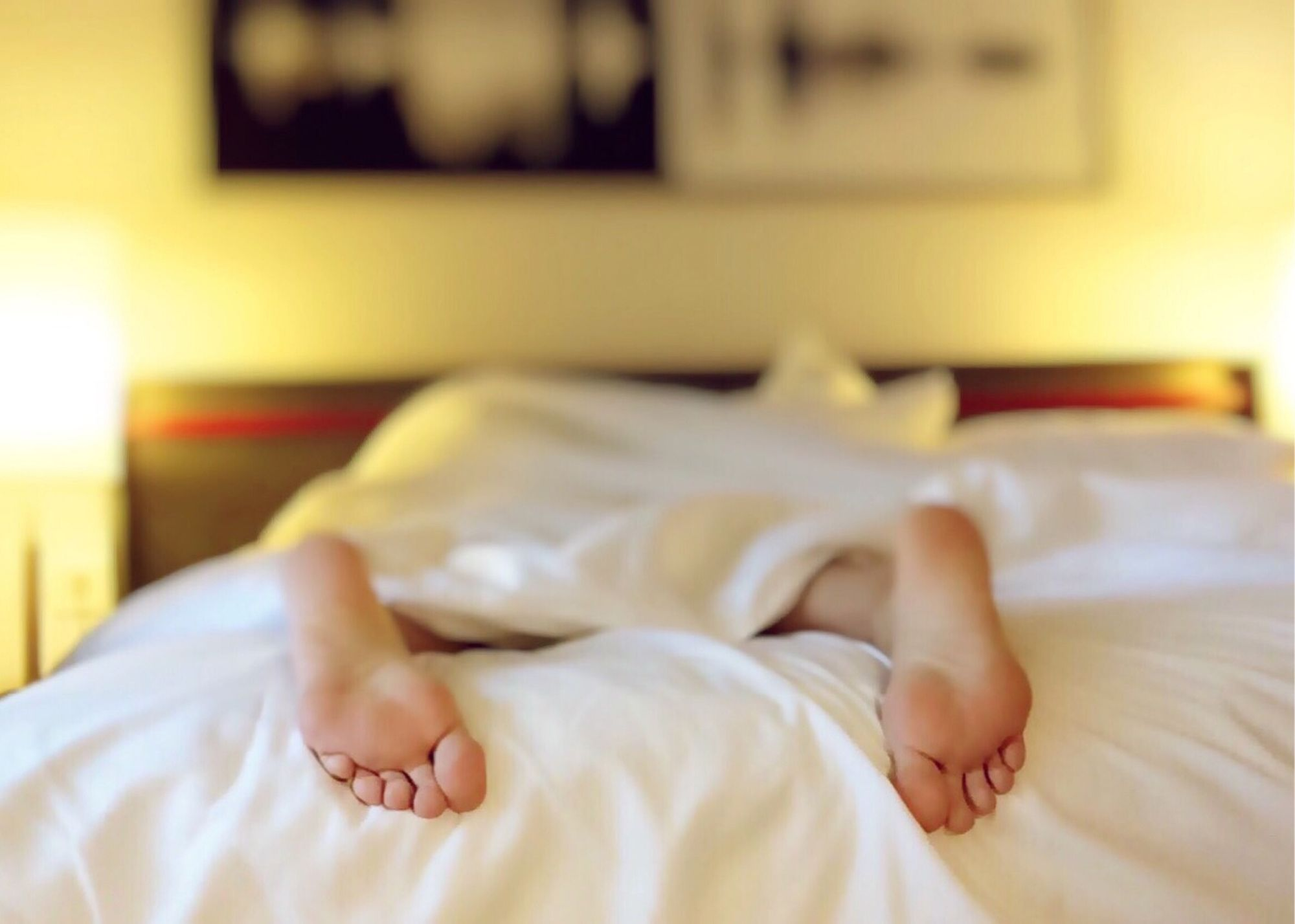 The Benefits of Melatonin - Person's feet Under Covers On Bed